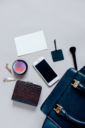 Flat lay of black leather woman bag open out with cosmetics, accessories and smartphone and blank card of paper on grey background with copy space