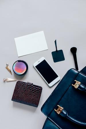 Plat zwart lederen vrouw tas te openen met cosmetica, accessoires en smartphone en blanco kaart papier op een grijze achtergrond met een kopie ruimte Stockfoto