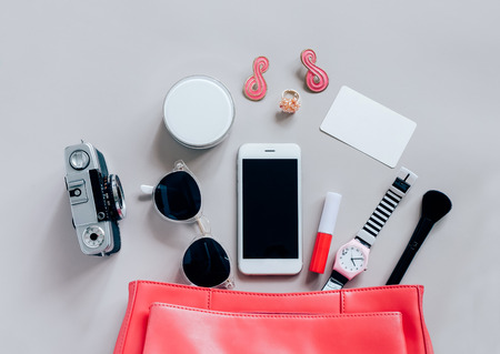 Flat lay of pink leather woman bag open out with cosmetics, accessories, tag card and smartphone on grey background with copy space Banque d'images