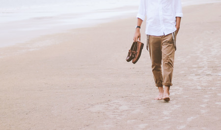 Alone man walking on the beach carrying leather shoes  Stock Photo