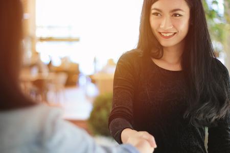 Happy asian businesswoman handshake with partner, negotiating business concept