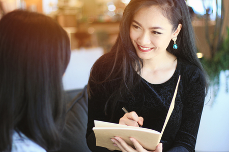 People and service concept, young asian businesswoman filling the information on paperwork for customer Stock Photo