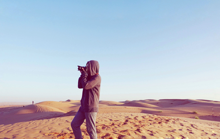 wanderlust: Woman photographer taking photos on beautiful landscape sand dune desert in Oman