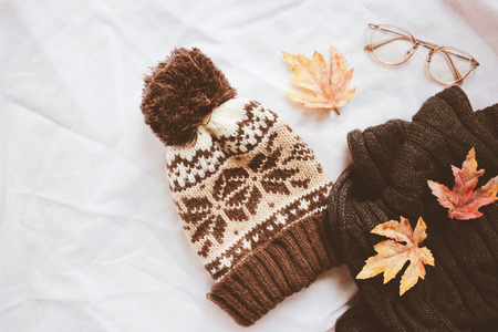 Flat lay of autumn fashion style, scarf, knitted hat and eyeglasses with maple leaves on white sheet background 免版税图像