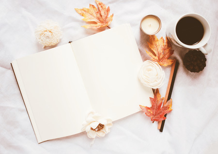Autumn lifestyle concept, blank notebook and coffee with autumn leaves ornaments on white bed sheet background
