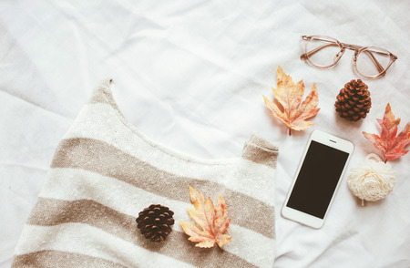 Autumn fashion style concept, sweater and smartphone with maple leaves on white bed sheet background