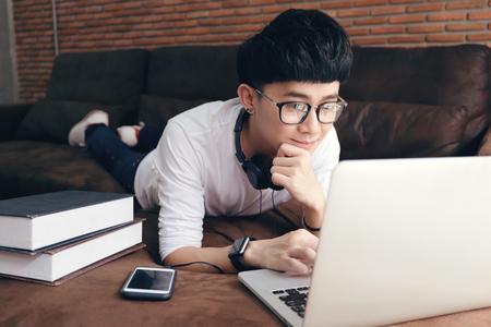 Joven universitario asiático acostado en un sofá y el uso de la computadora portátil mientras se hace la tarea en la sala de estar moderna