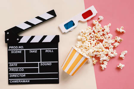 Flat lay of cinema items, clapperboard, 3d glasses and popcorn on colorful bright background, entertainment concept Stock Photo