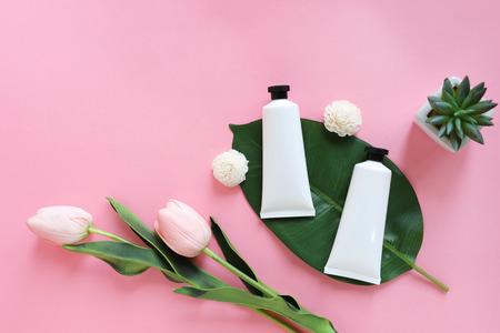 Mise à plat de produits de soin de beauté pour des maquettes dans un style minimal avec des plantes et des fleurs sur fond rose
