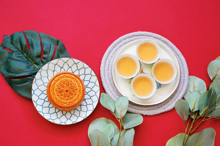 Flat lay of chinese moon cake with hot tea and green plant on red background, holiday and festival concept