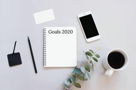 Objetivos de 2020 en una foto plana del escritorio del espacio de trabajo con teléfono inteligente, café, tarjeta y cuaderno con fondo de espacio de copia, estilo minimalista y concepto de maqueta