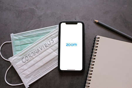 BANGKOK, Thailand - April 2, 2020 : Flat lay of smartphone showing zoom application and mask with notebook. Zoom is popular cloud meeting or video conference during COVID-19 and Coronavirus