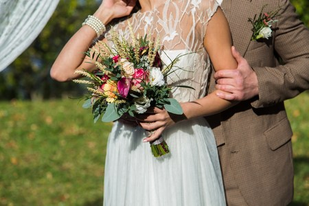 bouqet: Bride and groom with wedding bouqet, closeup shot Stock Photo