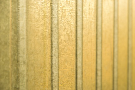 holed: Corrugated yellow metal sheet wall background texture