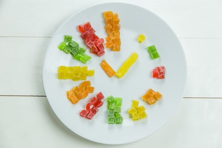 candied fruits: Fruit clock with candied fruits on wooden white background Stock Photo