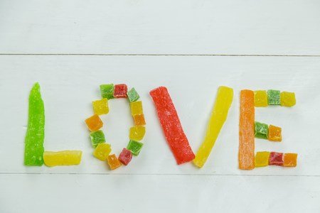 candied fruits: Love word with candied fruits on wooden white background