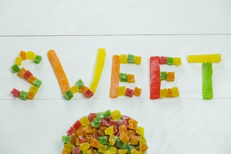 candied fruits: Sweet word with candied fruits on wooden white background
