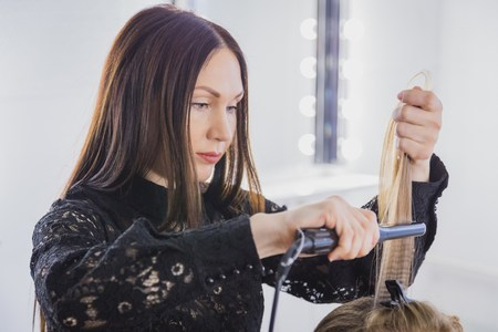 fluting: Beautiful young woman is getting her hair straightened at beauty saloon. The hairdresser is standing and holding a fluting iron