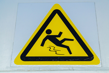 warning sign, caution wet floor at white wall Stock Photo