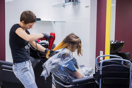 Professional hairdresser, stylist drying client hair with blow-dryer at salon, studio. Beauty and haircare concept Foto de archivo