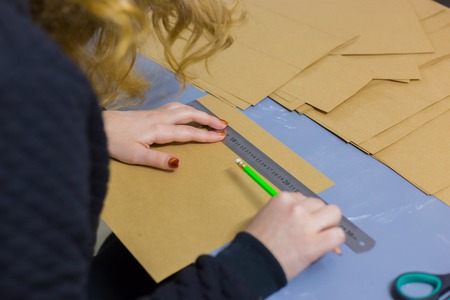 Close up shot - professional woman decorator, designer working with kraft paper and making envelope at workshop, studio. Design, handmade and art concept