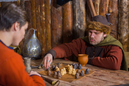 Two men in russian ethnic suit playing medieval popular strategy board game - tafl. Folk, competition and traditional concept Standard-Bild - 120952967