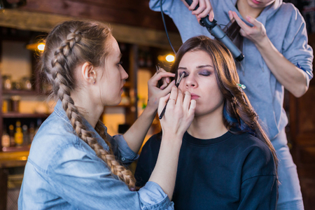 Professional make-up artist and hairdresser working with woman client. Beauty, haircare and make up concept 版權商用圖片
