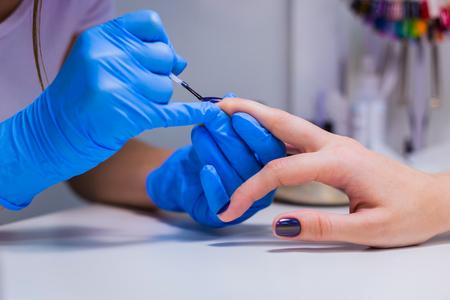 Professional beautician applying nail polish to female nail in a nail salon. Imagens