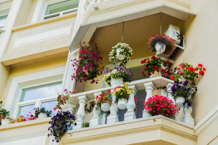 Balcon with beautiful flowers, white house in town Foto de archivo - 120966040