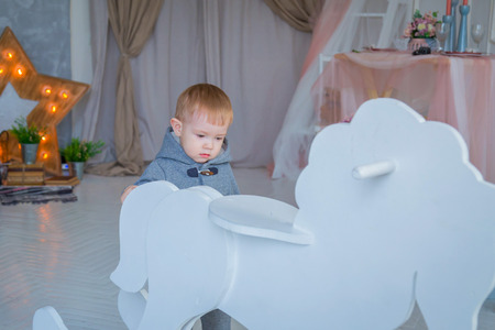 Little boy playing with white wooden rocking horse