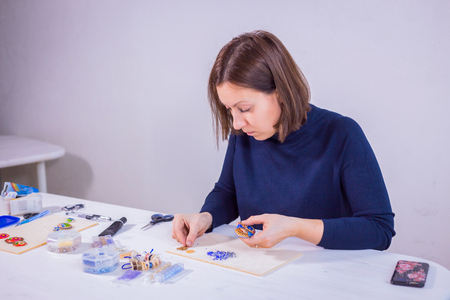 Professional jewelry designer making handmade brooch in traditional russian style with beads in studio, workshop. Traditional, creativity, folklore and handmade concept