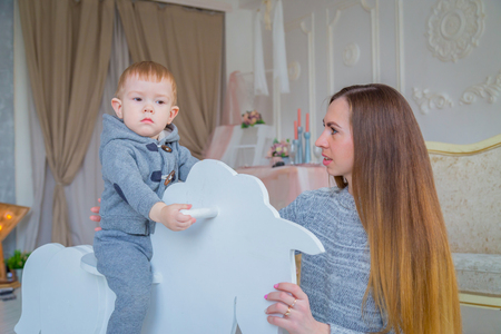 Little boy playing on white wooden rocking horse with him mother Stock Photo - 123426275