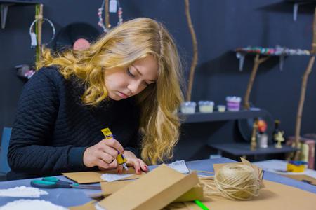 Mujer decoradora profesional, diseñadora que trabaja con papel kraft y hace sobres en el taller, estudio. Diseño, artesanía y concepto artístico.