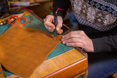 Professional male skinner, tanner making decorative details on leather playing field for strategy board game -tafl with special pyrographic machine Stock fotó
