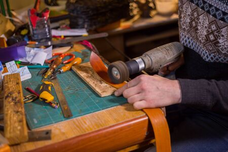 Professional male skinner, tanner working with genuine leather belt at workshop, studio. Handmade and leatherwork concept
