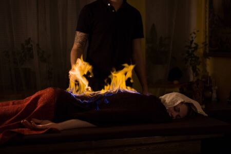 Chinese fire massage - Huo Liao therapy. Traditional chinese medicine, fire treatment and bodycare concept 免版税图像