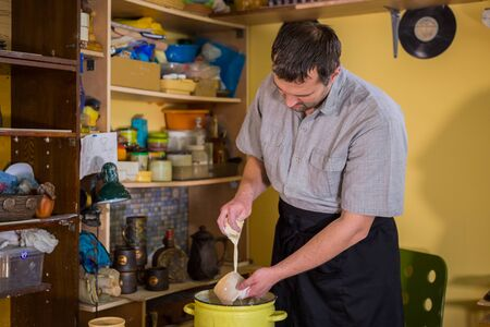 Professional male potter preparing ceramic wares for burning in pottery kiln with milk - old russian pottery tradition. Crafting, artwork and handmade concept