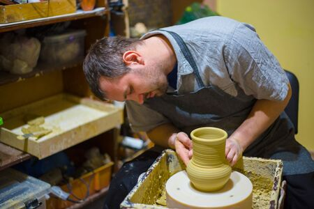 Professional male potter making jug in pottery workshop, studio. Handmade, art and handicraft concept