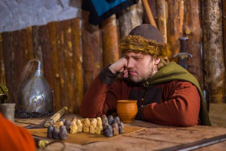Portrait of man in russian ethnic suit playing board game like chess. Folk, competition and traditional concept