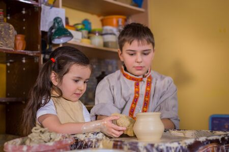 Pottery class and workshop: children trying to make ceramic wares in pottery studio. Handmade, education and study concept