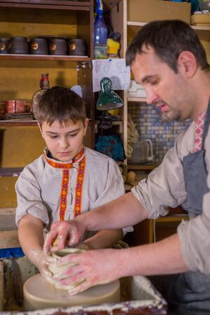 Pottery class and workshop: professional male potter working with boy and showing how to make ceramic wares in pottery studio. Handmade, education and study concept Foto de archivo
