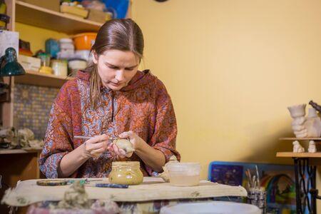 Potier professionnel faisant des souvenirs en céramique penny whistle jouet oiseau dans l'atelier de poterie, studio. Artisanat, œuvres d'art et concept artisanal
