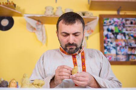Professional male potter in russian ethnic shirt making clay figure for medieval popular strategy board game - tafl. Handwork, crafting and traditional arts concept