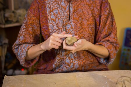 Professional woman potter making ceramic souvenir penny whistle toy bird in pottery workshop, studio. Crafting, artwork and handmade concept Foto de archivo