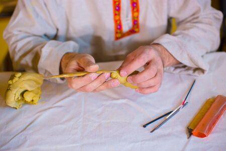Potier professionnel en chemise ethnique russe faisant figure d'argile pour jeu de société de stratégie populaire médiéval - tafl Concept de travail manuel, d'artisanat et d'arts traditionnels