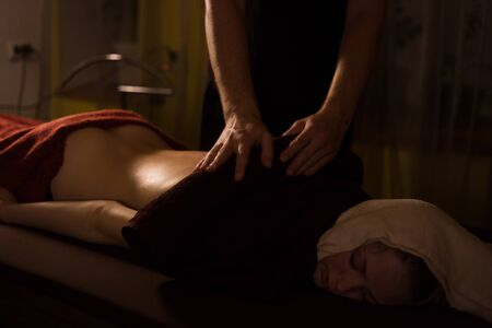 Professional male masseur doing massage for woman client with hot towel at spa salon, studio. Warm romantic illumination, low key. Wellness, relaxation and healthcare concept Reklamní fotografie