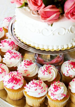 cor: White wedding cake with pink roses and cupcakes