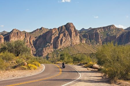 Motorcycle riding through Arizona desert landscape with jagged mountains ahead Stock Photo