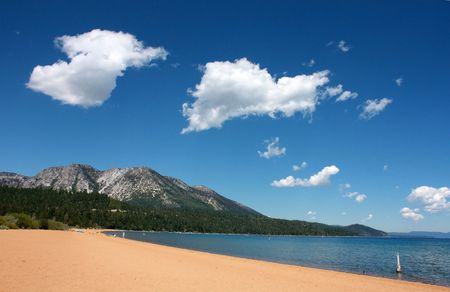 Lake Tahoe beach on a sunny day wtih blue skies and silky clouds Stock Photo