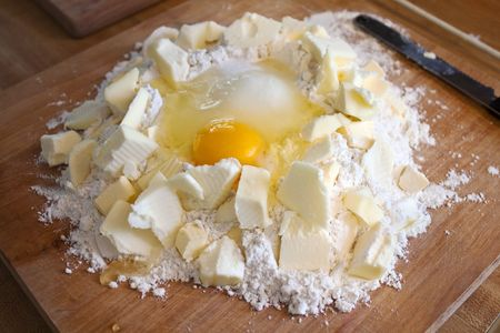 Well of flour with egg in the middle surrounded by flakes of butter Stock Photo